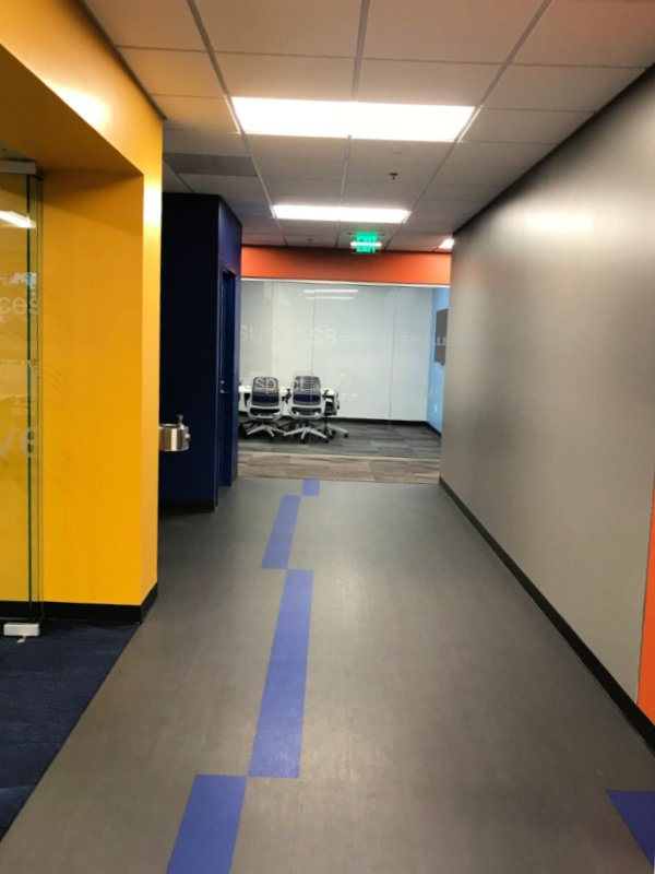 Telecommunication Company Headquarters hallway done in themed grey flooring with a blue directional stripe in the project by The Blue River Group