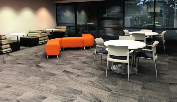 The Telecommunications Company Headquarters break room with tables and booths done in yellow and grey with orange for a pop of color