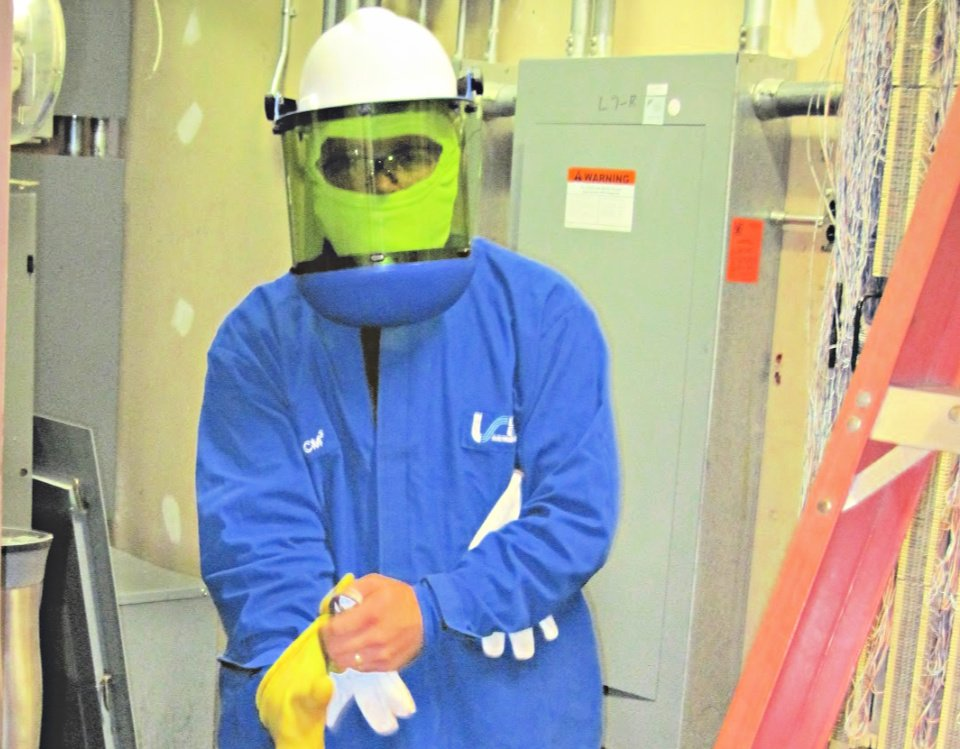 The Blue River Group employee putting on safety equipment including helmet, face shield, mask, and gloves