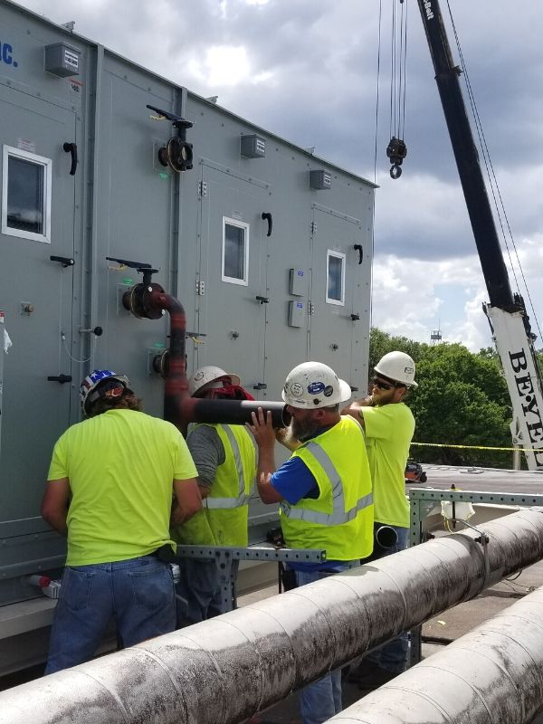The Blue River Group Services Mechanical Subcontractor making chilled water piping connections to new air handling unit.