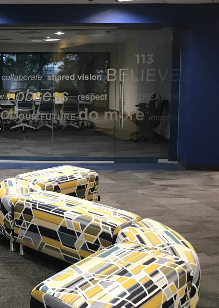 A custom yellow and grey geometric settee outside of a conference room of a Blue River Group Featured Project